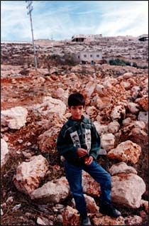 A Palestinian youth awaits the fate of hishome in the West Bank, set to be demolished by area settlers.