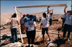 Israeli and American volunteers help to build a makeshift home for a Palestinian family whose house was demolished by the Israeli government.
