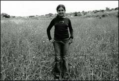 Meerna al-Azzah stands in a field in the abandoned village of Beit Jibrin, where her family lived before the war in 1948.