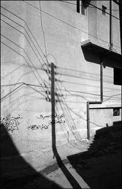 The shadow of a telephone pole cast against a wall of political graffiti in Dheisheh refugee camp.