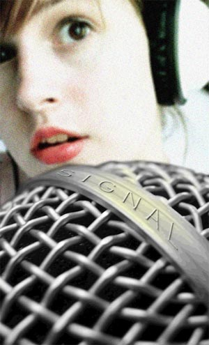 Woman in headphones with microphone labeled Signal
