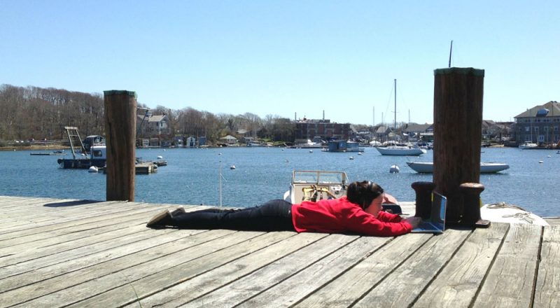 Lilly editing on the dock. Photo by Transom alum Karen Duffin