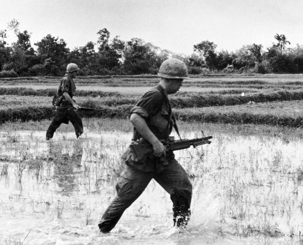 Unidentified soldiers march through rice fields. Photo by Earl Van Alstine