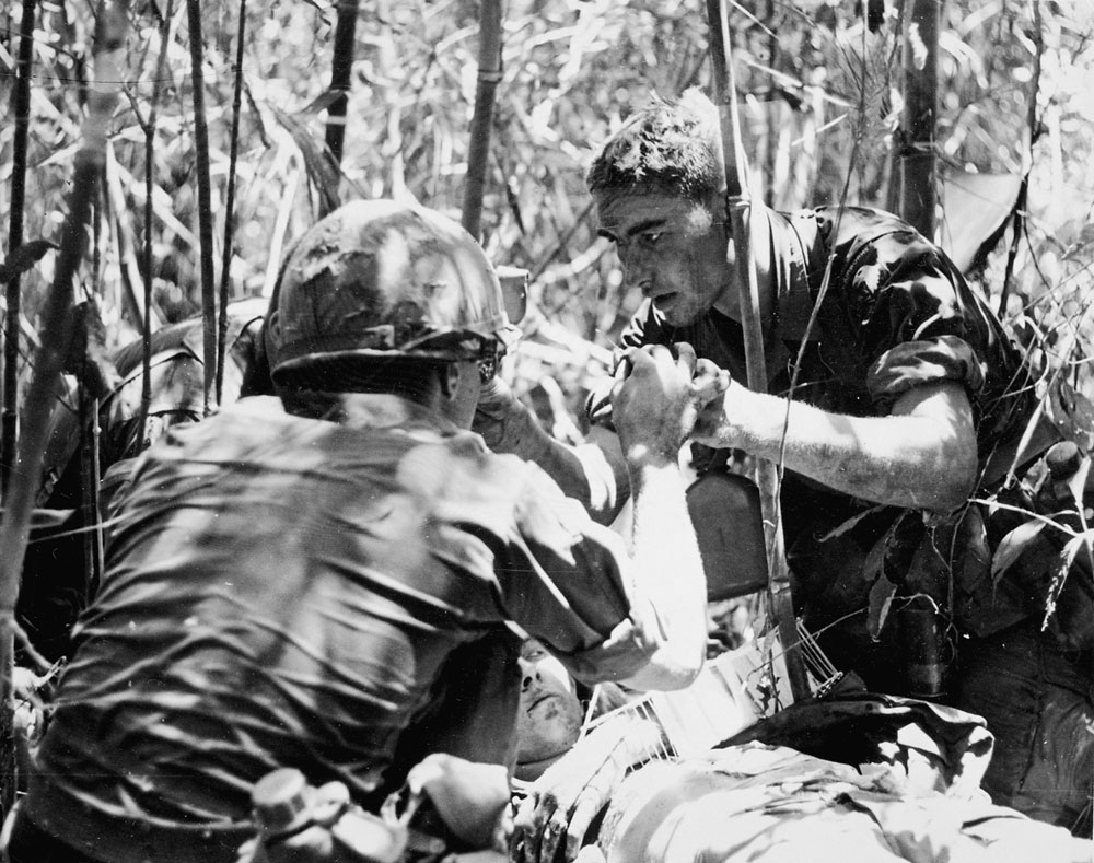 Medic Ken Kotyluk, senior medic for Charlie Company, tends to a wounded soldier. The soldier's arm would later be amputated at the elbow. The medic is believed to have been killed a month later. Photo by Earl Van Alstine