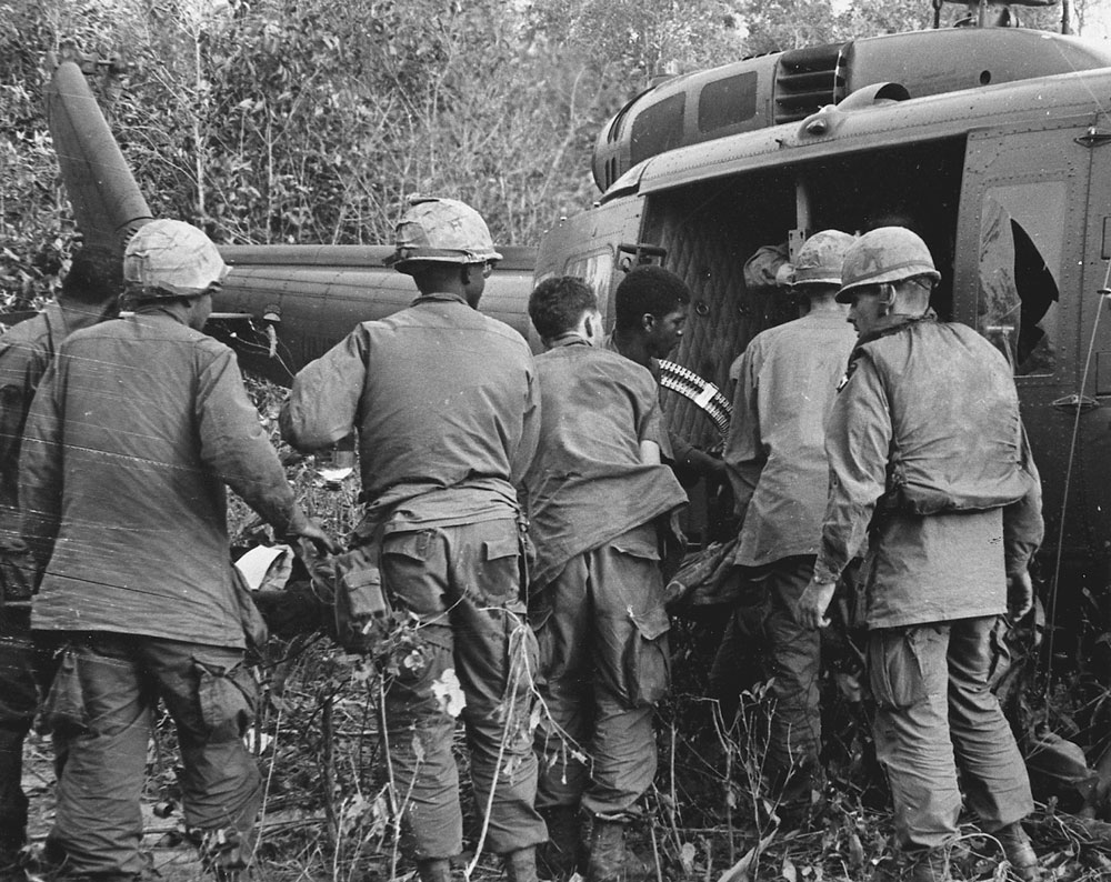 Bud Bucha (in profile far right) as soldiers load Calvin Heath, Jeff Wishik, and Bobby Deitch onto a helicopter. Photo by Earl Van Alstine
