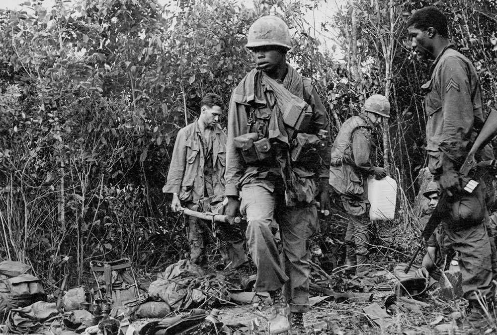 Soldiers carry stretcher loaded with equipment of the dead. Photo by Earl Van Alstine