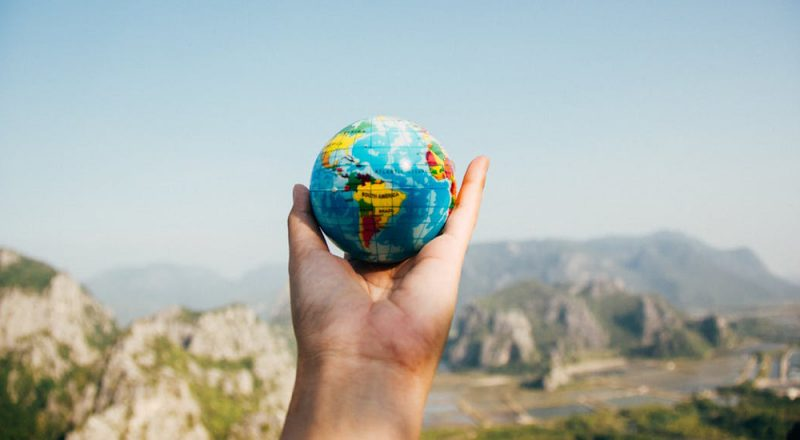 photo of hand holding a globe